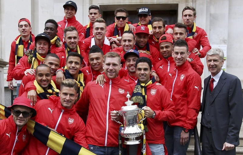 Arsenal players and their manager Arsene Wenger pose for a picture outside Islington Town hall with the trophy during a victory parade after winning their FA Cup final soccer match yesterday, in north London, Britain, May 31, 2015. REUTERS/Neil  Hall